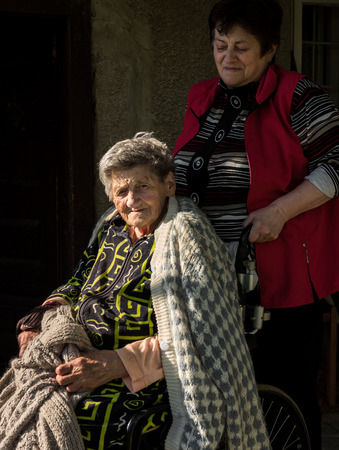 Old woman in a wheelchair and her daughter near the house photo