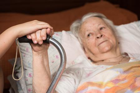 Caring handen die handen oude vrouw in bed thuis