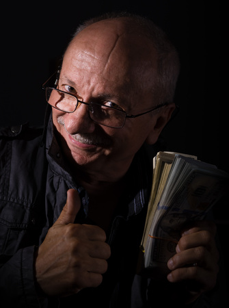 sly: Sly senior man holding dollar bills on a dark  background
