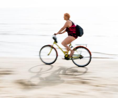 intentional: Female biker having a ride along the beach. Intentional motion blur