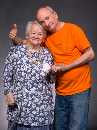 adoring: Smiling old mother with elderly son on a gray background