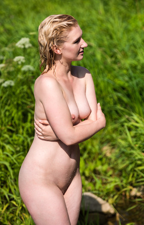 nude nature: Young beautiful nude woman posing on nature background. Enjoying summer time outdoors Stock Photo