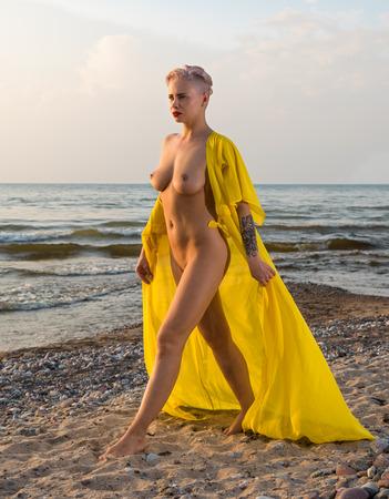 mujer rubia desnuda: joven y bella mujer rubia desnuda disfrutando del verano en la playa. Posando en traje de color amarillo