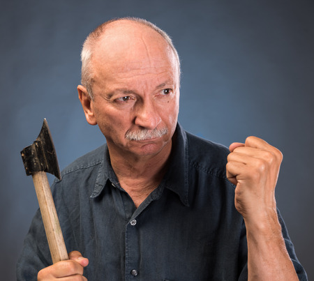revenge: Angry elderly man with an ax on a dark background