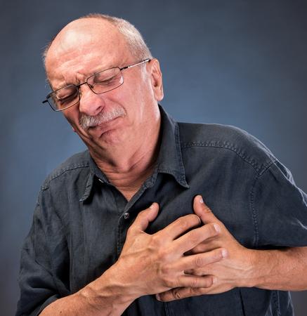 Elderly man in glasses having a heart attack