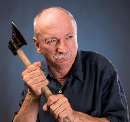 revenge: anciano enojado con un hacha sobre un fondo oscuro Foto de archivo