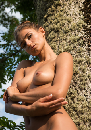 Young nude woman posing near the tree. Enjoying nature and summer time