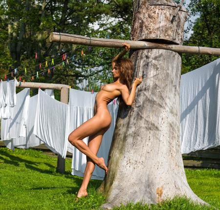 Hermosa joven mujer desnuda que presenta contra la ropa de cama de secado. disfrutando de verano
