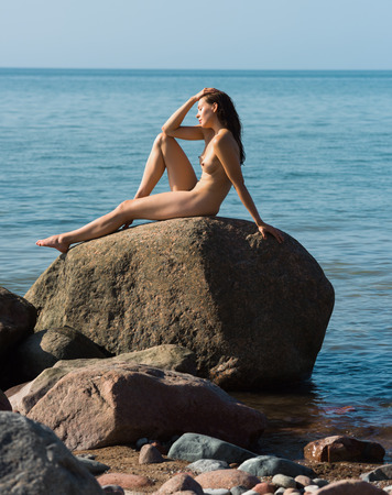 nude nature: Beautiful young naked woman posing on the beach. Enjoying summer time near the sea