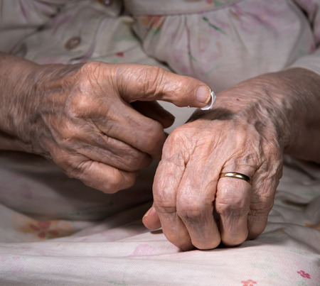 liniment: Old woman applying hand cream at home