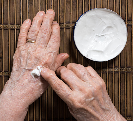 unguent: Close up of old womans  hands applying cream at home