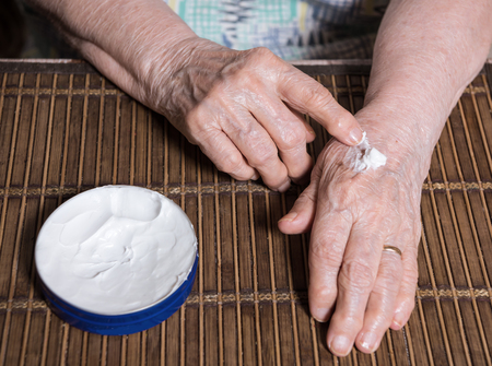 liniment: Close up of old womans  hands applying cream at home