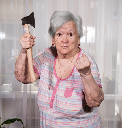 Angry old man with an ax posing at home