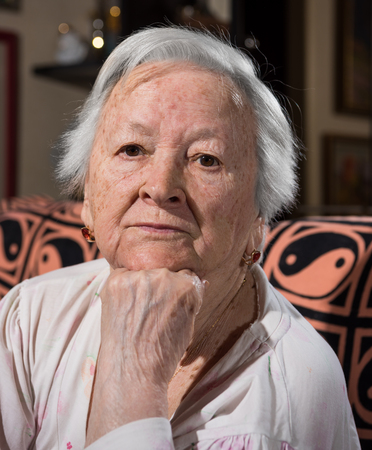 Portrait of old sad woman at home. Sick depressed old woman Stock Photo