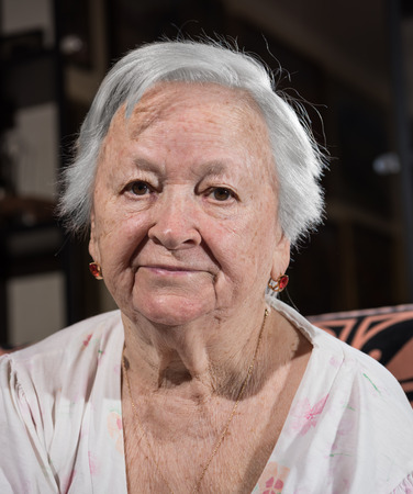 saddened: Portrait of old sad woman at home. Sick depressed old woman Stock Photo
