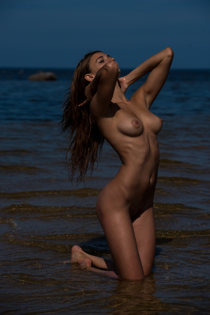 nude nature: Beautiful young sexy nude woman posing in the sea. Enjoying summertime