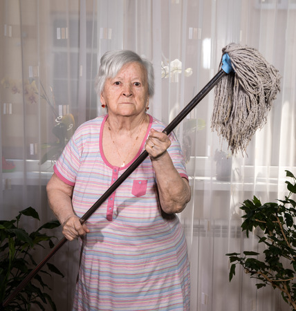 Old angry woman threatening with a mop at home