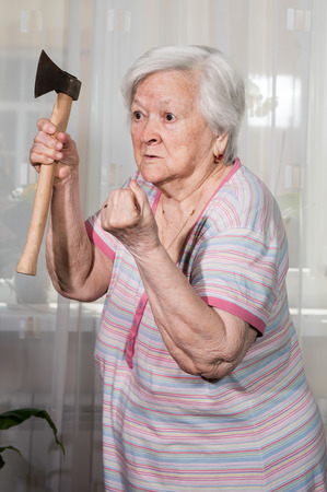 Angry old woman with an ax posing at home