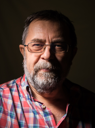 Beard elderly man in glasses posing on a dark background photo