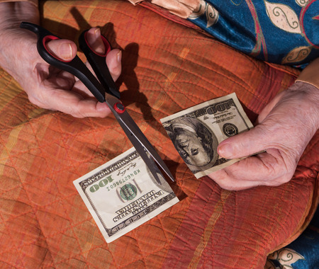 Close-up of old woman holding torned one hundred dollar bill