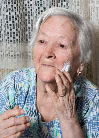 antiaging: Old woman applying anti-aging cream at home Stock Photo