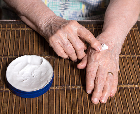 liniment: Old woman applying hand cream at home. Close-up of wrinkled womans hands Stock Photo