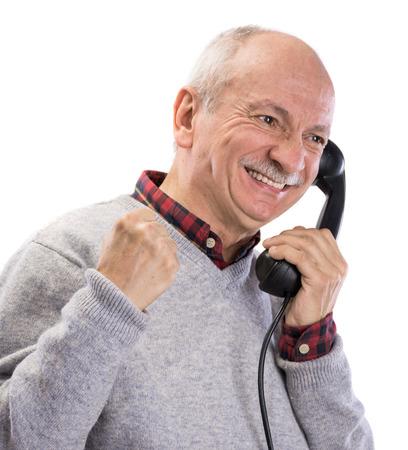 Portrait of happy senior man  talking on old landline phone on a white background