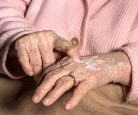 unguent: Old woman applying hand cream at home. Close-up of wrinkled womans hands Stock Photo