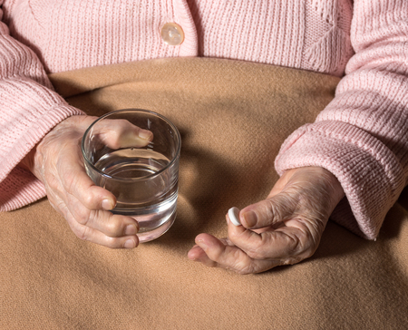 heartattack: Old sick woman with pills and glass of water at home