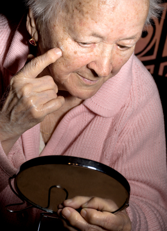 antiaging: Portrait of old woman looking into a mirror and applying anti-aging cream at home