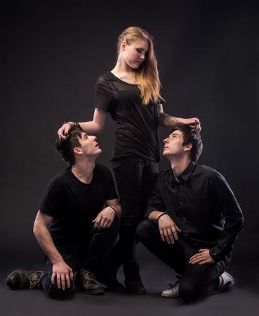 Triángulo amoroso. Mujer joven que presenta con dos hombre joven en un fondo oscuro