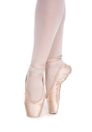 pies bailando: The close-up of ballerina in pointe shoes  posing on a white background