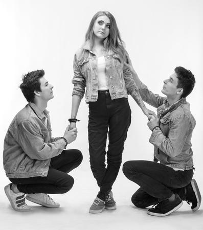 Triángulo amoroso. Mujer joven que presenta con dos hombre joven en un fondo blanco en el estudio