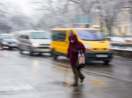 intentional: Woman with a cane on zebra crossing in a rainy day. Intentional motion blur