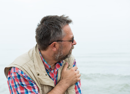 Thoughtful senior man posing at the beach on a foggy day photo