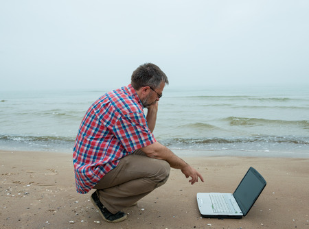 Senior businessman sitting with notebook at the beach photo