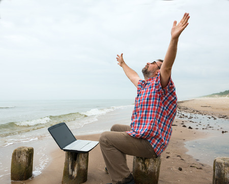 Senior happy man sitting at the beach with laptop on a foggy day photo