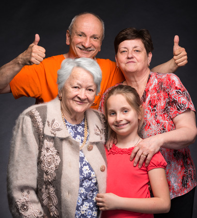 Happy multi-generation family posing in studio on a gray background photo