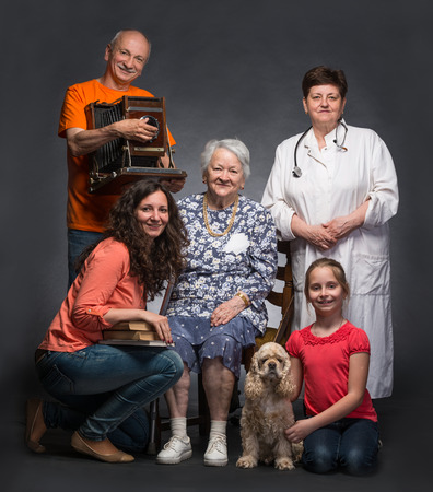 Happy multi-generation family and pet dog posing in studio on a gray background photo