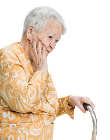 Old sad woman standing with a cane posing on a white background