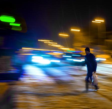 Hombre en el paso de cebra en la noche. Desenfoque de movimiento intencional