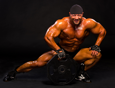 Handsome bodybuilder posing in studio with barbell weight on a dark background.