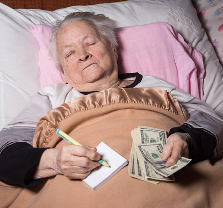 Old woman lying in bed. Holding dollar cash money and notebook with pen at home