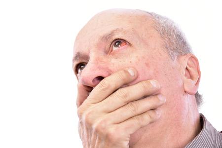 hombre sorprendido mayor con los ojos inyectados en sangre irritada rojo sobre un fondo blanco Foto de archivo
