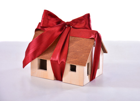 realestate: Small model of a wooden house tied with a bow isolated on white . Eco house