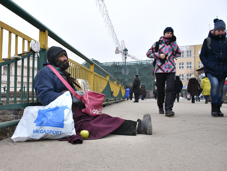 UZHGOROD,UKRAINE - FEBRUARY 16, 2017: Poor man begging for alms in the street of Uzhhorod, Ukraine. Beggar sitting on the ground