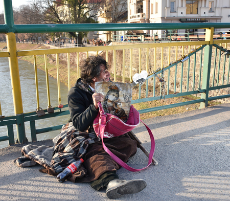 UZHGOROD,UKRAINE - MARCH 04, 2017: Poor man begging for alms in the street of Uzhhorod, Ukraine. Beggar sitting on the ground