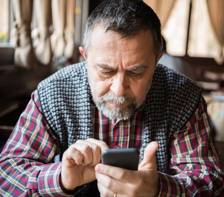 Senior man using a smart phone photo