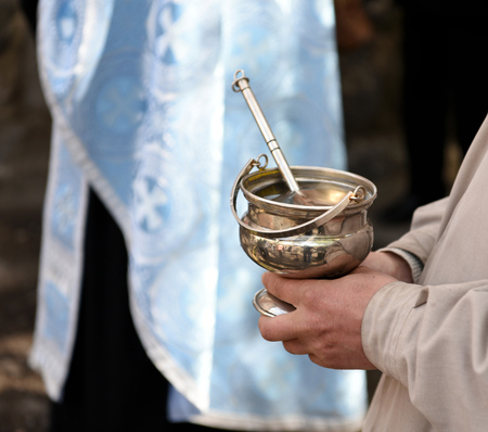 cassock: Male hands of priest  holding silver bowl and spoon on the  ceremony