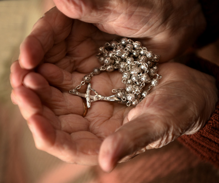 Close up of old woman praying with silver rosary with cross  in her hands at home.Sick woman calling to God Stock Photo